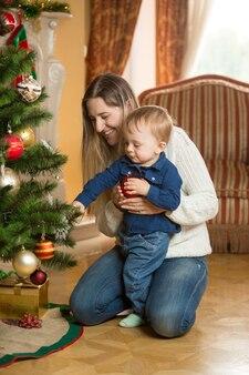 Matka pokazuje swojemu synkowi, jak ozdobić choinkę bombkami