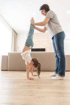 Matka pomaga córce chodzić do góry nogami na rękach w domu trzymając nogi