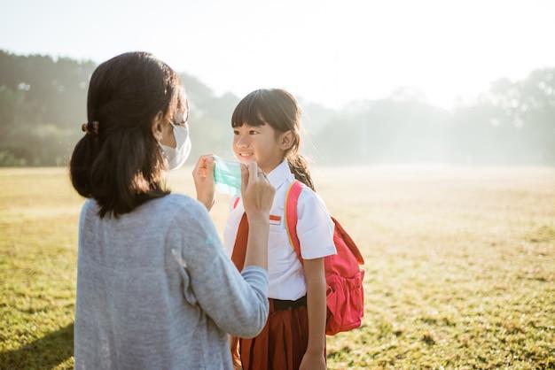 Matka pomaga córce założyć maskę przed pójściem do szkoły