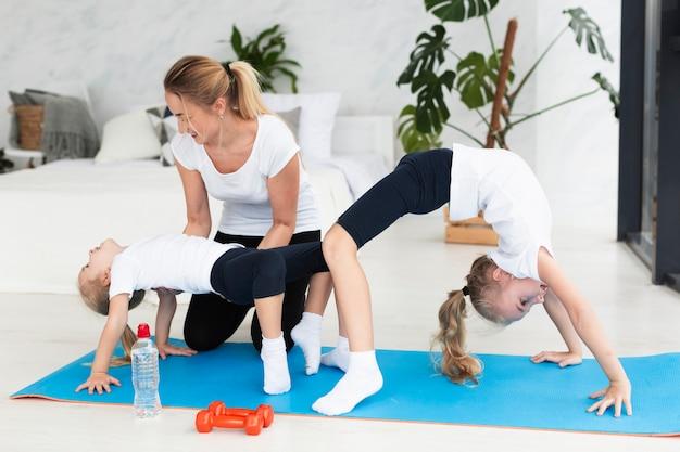 Matka pomaga córkom ćwiczyć w domu