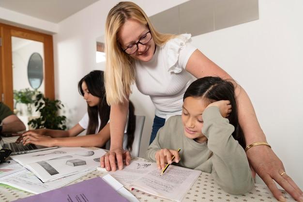 Matka pomaga córkom w odrabianiu prac domowych