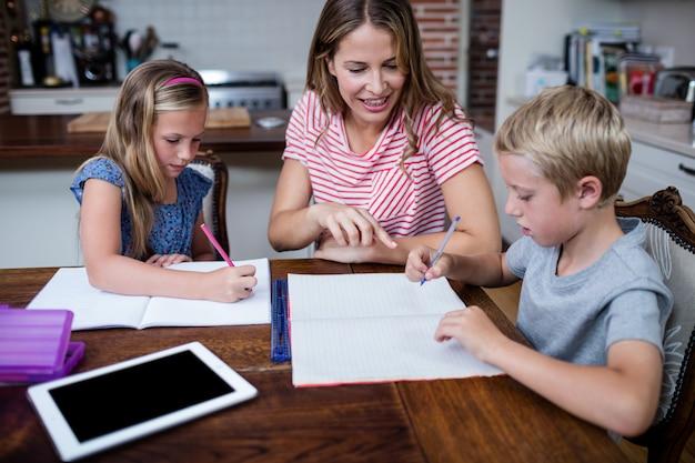 Matka pomaga dzieciom w odrabianiu lekcji