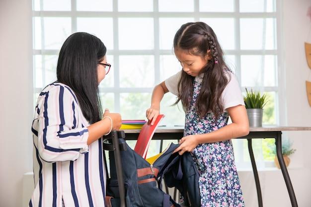 Matka pomaga dziewczyna szkoły podstawowej pakowania książek do torby