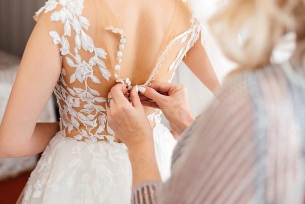 Matka pomaga pannie młodej z suknią ślubną