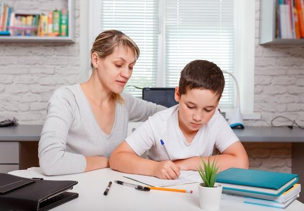 Matka pomaga synowi robić lekcje. wychowawca angażuje się z dzieckiem, uczy pisania i liczenia.