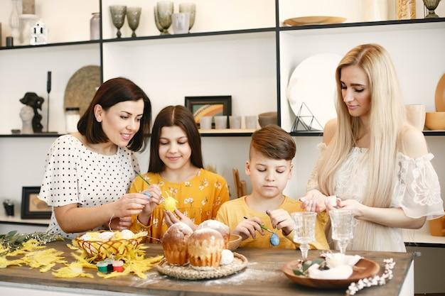Matka pomaga synowi rysować. dzieci przy stole. mama jest blondynką.