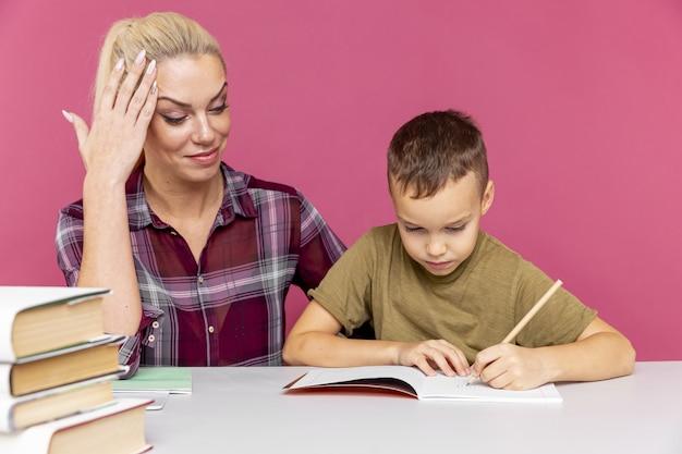 Matka pomaga synowi uczyć się w domu. szkoła zamknięta z powodu kwarantanny.