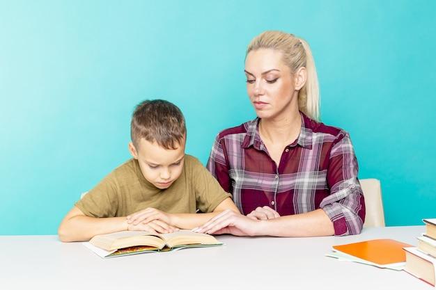 Matka pomaga synowi w odrabianiu prac domowych na na białym tle różowym. daleka edukacja.