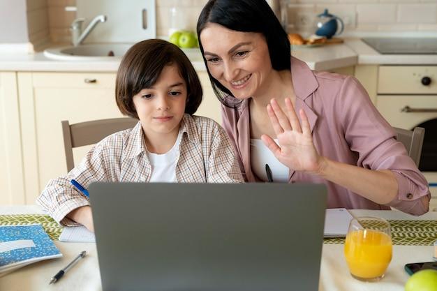 Matka pomaga synowi w zajęciach online