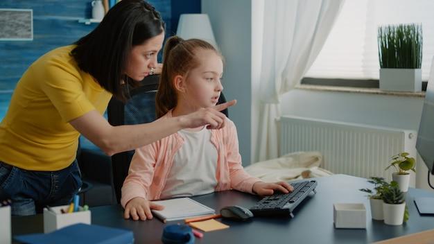 Matka pomagająca małemu dziecku w odrabianiu prac domowych do zdalnej edukacji