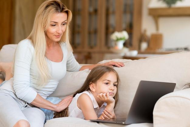 Matka, pozwalając córce patrzeć na laptopa podczas pracy w domu