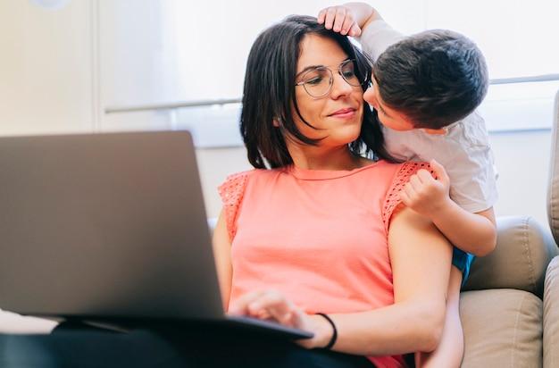 Matka Pracuje Na Sofie W Domu Przy Komputerze, A Syn Bawi Się Z Nią Premium Zdjęcia