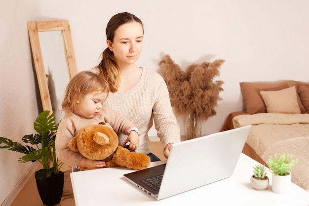 Matka Pracuje W Domu Na Laptopa, Dziecko Uniemożliwia Pracę, Młoda Kobieta Jest Z Nią Na Własny Rachunek Premium Zdjęcia