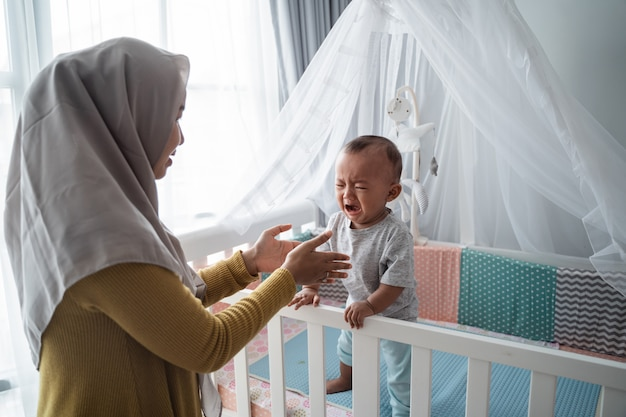Matka próbuje pocieszyć swoje płaczące dziecko w łóżeczku