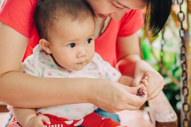 Matka próbuje przyciąć sobie paznokcie dla jej 7 miesięcznego dziecka