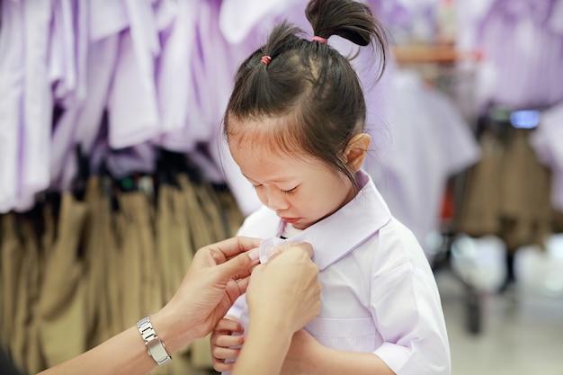 Matka próbuje ubrać szkolny mundurek dla swojej córki, dzieci w wieku przedszkolnym.
