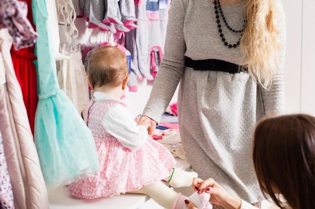 Matka próbuje założyć skarpetki córeczce w sklepie odzieżowym