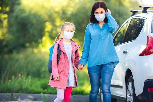 Matka prowadzi córkę do szkoły w maskach