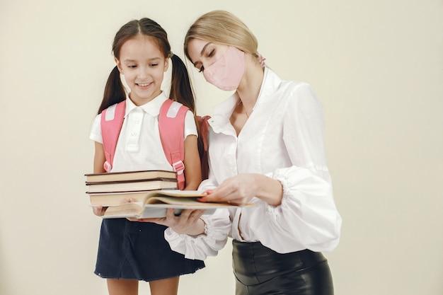 Matka przygotowuje córkę do nauki w szkole. odosobniony. kobieta w masce.