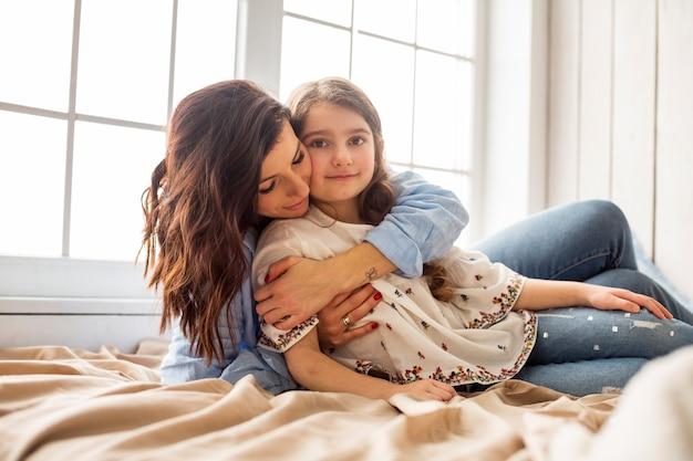 Matka przytulanie córki od tyłu na łóżku