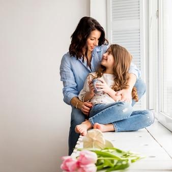Matka przytulanie córki od tyłu na parapecie