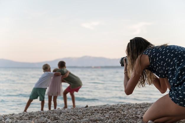Matka robi zdjęcia trojgu jej dzieci przytulających się i bawiących się na kamienistej plaży o zachodzie słońca.
