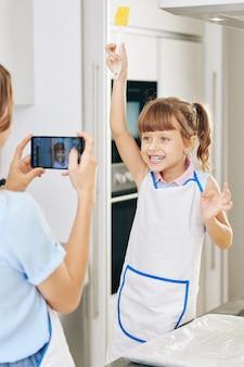 Matka robi zdjęcie śmiesznej dziewczyny z mąki na nosie z silikonową szczoteczką w kuchni