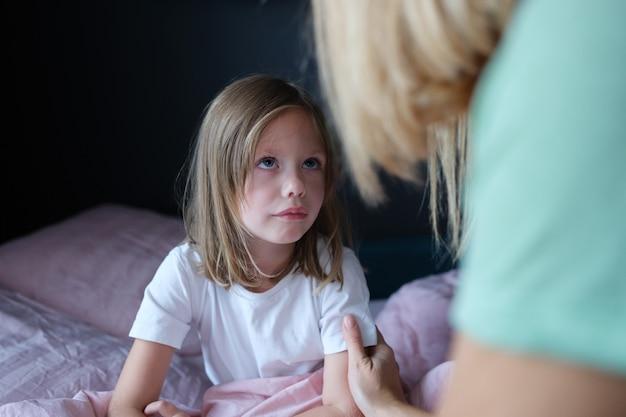 Matka rozmawia ze smutną małą dziewczynką w łóżku