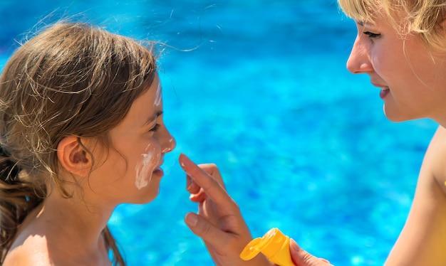 Matka rozmazuje krem przeciwsłoneczny na twarzy dziecka. selektywne skupienie. dziecko.