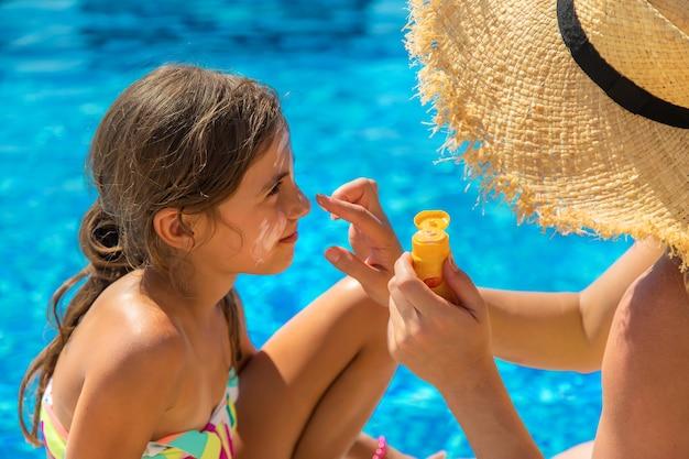 Matka rozmazuje krem przeciwsłoneczny na twarzy dziecka. selektywne skupienie.