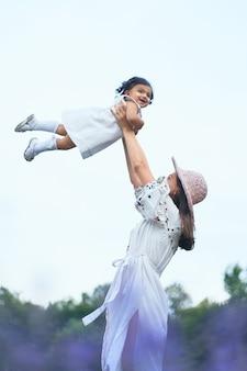 Matka rzuca córeczkę w lawendowym polu