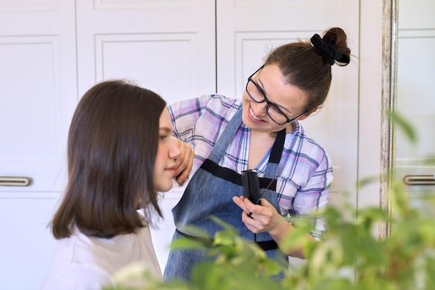 Matka ścina włosy nastoletniej córce, uroda i pielęgnacja w domu.