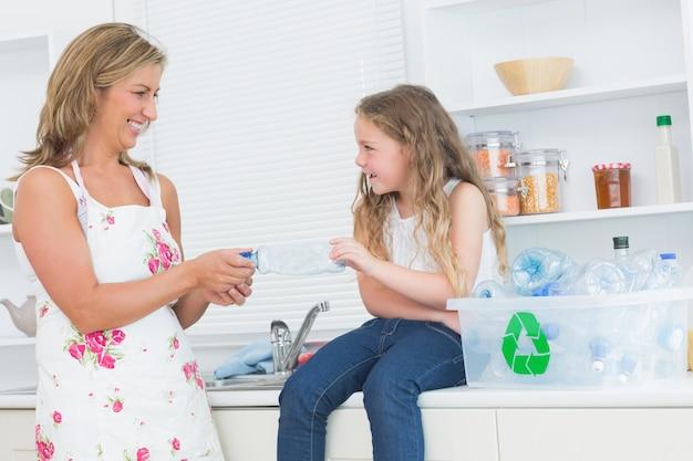 Matka segreguje odpady tworzyw sztucznych wraz z córką