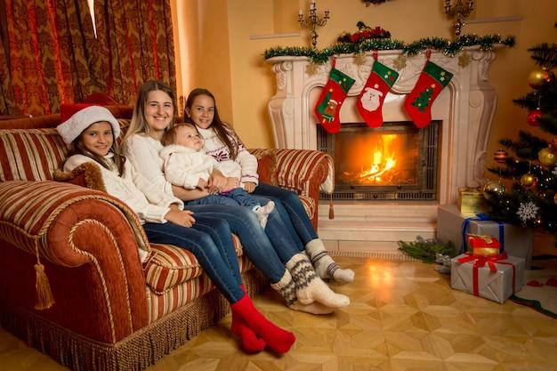 Matka siedzi z córkami na kanapie w salonie obok płonącego kominka w boże narodzenie