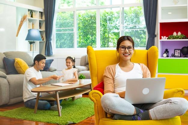 Matka siedzieć i pracować w domu na żółtej kanapie. azjatycka rodzina razem robi aktywność.