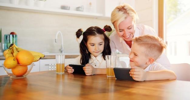 Matka, siostra i brat oglądają razem wideo na telefonie komórkowym.
