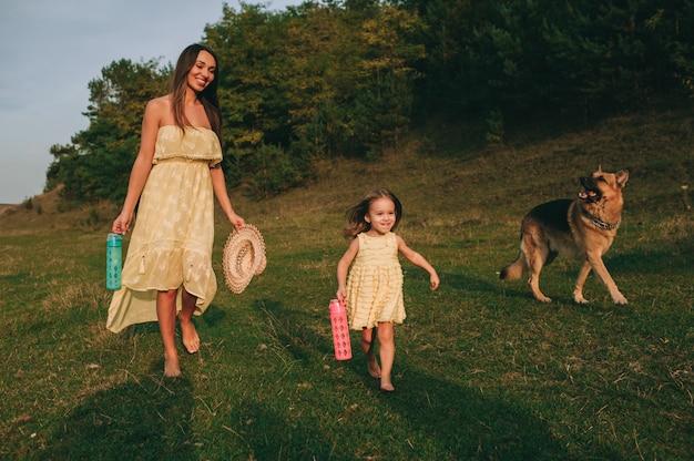 Matka spaceruje z córeczką i psem