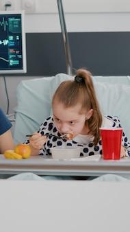Matka stojąca z chorą córką podczas jedzenia zdrowego posiłku podczas obiadu