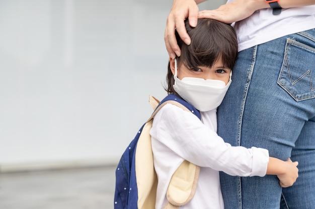 Matka towarzyszy dziecku do szkoły. mama wspiera i motywuje ucznia. mała dziewczynka w masce na twarz nie chce opuścić matki. obawia się szkoły podstawowej.