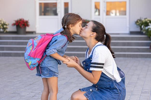 Matka towarzyszy uczniowi do szkoły, szczęśliwa dziewczynka z troskliwą mamą, z powrotem do szkoły.