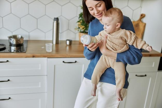 Matka trzyma butelkę z mlekiem dla jej noworodka. młoda uśmiechnięta kobieta trzyma niemowlę dziecko w ubrania z dzianiny. wnętrze kuchni w mieszkaniu. pojęcie macierzyństwa i opieki nad dzieckiem