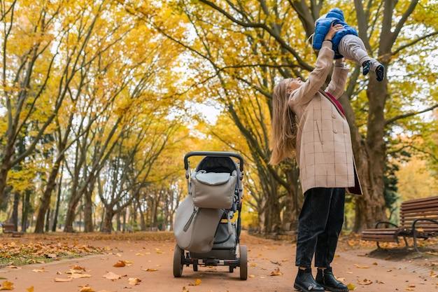 Matka trzyma dziecko w ramionach w parku