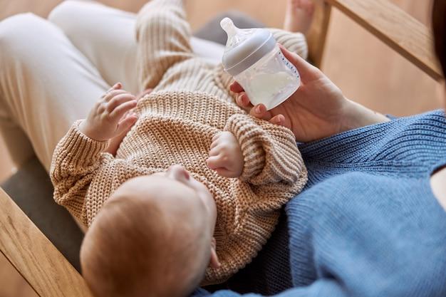 Matka trzyma jej nowo narodzonego dziecka i butelkę mleka. widok z góry kobiety i jej niemowlę dziecko siedzi w drewnianym fotelu. wnętrze apartamentu typu studio. pojęcie macierzyństwa i opieki nad dzieckiem