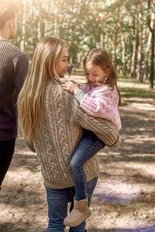 Matka trzyma na rękach roześmianą dwuletnią córkę. miły rodzinny spacer po lesie?