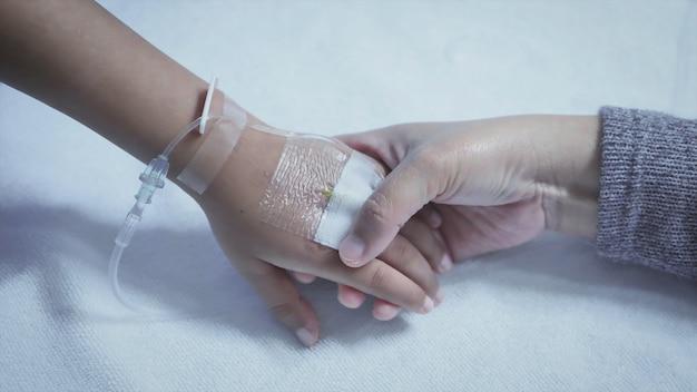 Matka trzyma rękę jego syna chorego łóżka w szpitalu. dotknij ręki. zachęta do opieki