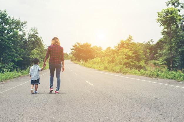 Matka trzyma rękę swojego syna w lecie dzień chodzenia na st