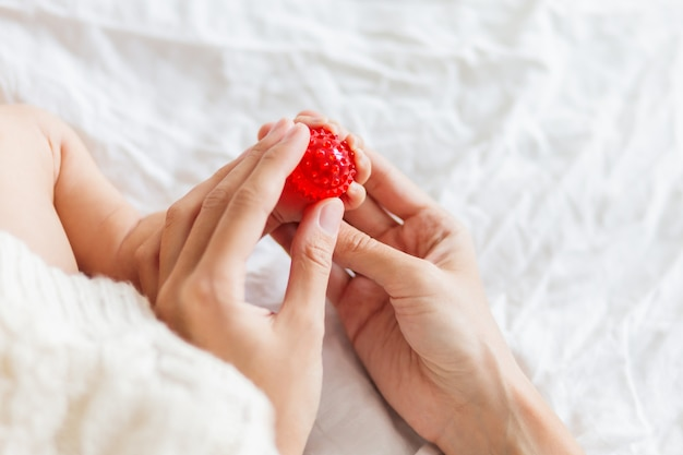 Matka trzyma stopy noworodka. małe palce i czerwona piłka do masażu w kobiecej dłoni.