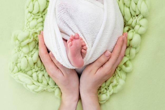 Matka trzyma stopy noworodka rękami, palcami na stopach, matczyną opieką, miłością i rodzinnymi uściskami, czułością. żółty
