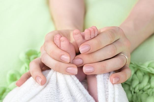 Matka trzyma stopy noworodka rękami, palcami na stopach, matczyną opieką, miłością i rodzinnymi uściskami, czułością.