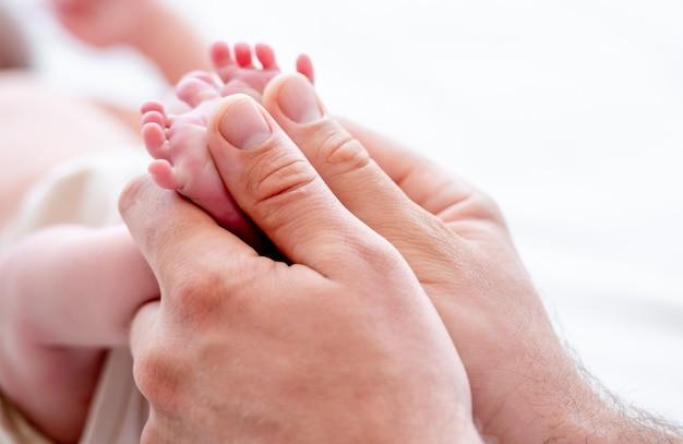 Matka trzyma stopy noworodka